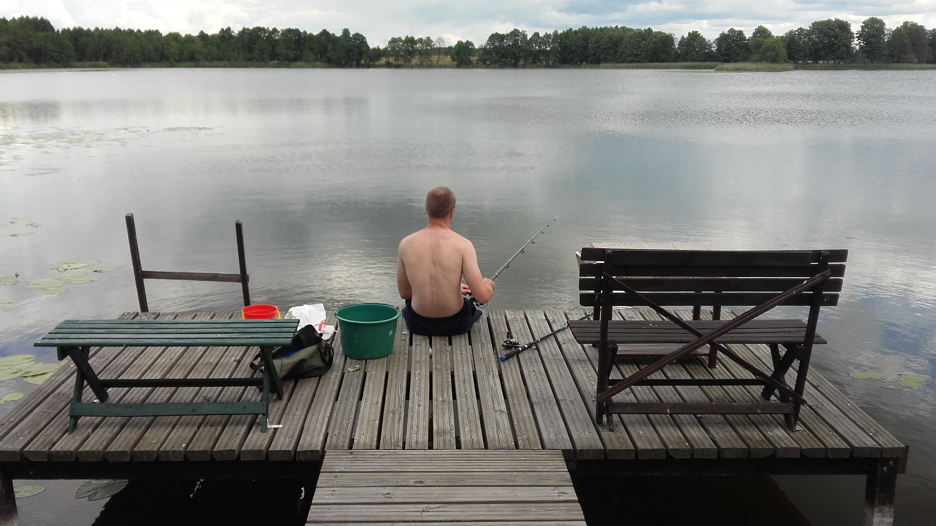 wędkarz łowi ryby z kładki. Weekend nad jeziorem Inulec